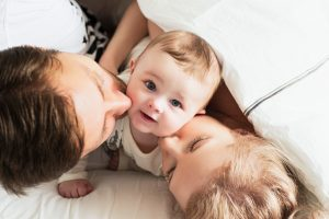 Parents kissing their baby