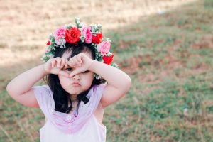 toddler girl with flowers on head and grumpy face, toddlers can have sleep struggles when they have no sense of control