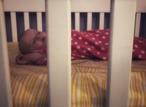 baby on back alone in crib with sleep sack